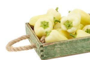 Green fresh bell peppers in the wooden tray, isolated