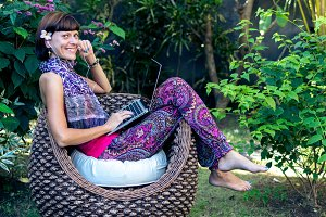 Young beautiful woman working with laptop at outdoor tropical park, smile and happy relaxing feeling in the morning, freelancer working businesswoman lifestyle concept. Bali island, Indonesia.