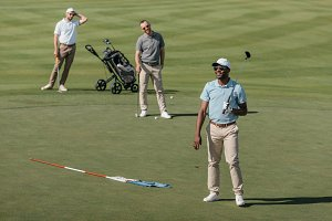 sportsmen standing with golf clubs