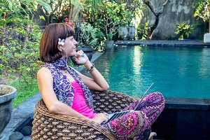 Sexy woman with laptop computer on a lounge near swimming pool outdoors. Tropical garden of Bali island, Indonesia.