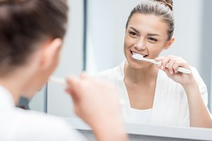 smiling woman brushing teeth