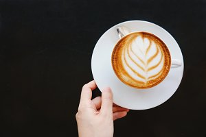 Woman hand with hot latte coffee