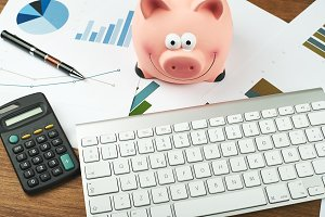 Business graphs next to computer keyboard, calculator, piggy bank and ball-point pen. Analysis of financial data.