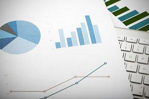 Business graphs next to computer keyboard. Financial data.