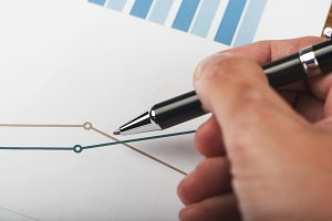 Close-up of business graphs and a male hand with a pen. Analysis of financial data.