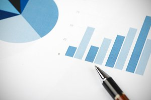 Business graphs next to  pen. Analysis of financial data.