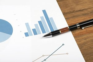 Close-up of business graphs next to  pen. Analysis of financial data.