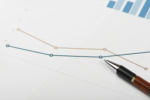 Close-up of business graphs next to  pen.