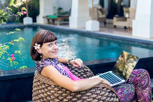 Sexy woman using laptop computer on a lounge near swimming pool outdoors. Tropical garden of Bali island, Indonesia.
