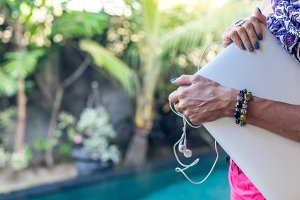 Woman holding laptop computer and headphones near swimming pool outdoors. Tropical garden of Bali island, Indonesia.