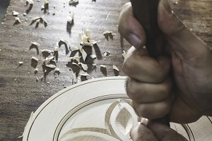 Hands of woodcarver make ​​wooden bo