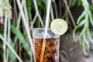Glass of coke drink with ice and lime on a nature background on a wooden table. Bali island.