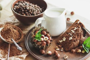 Piece of chocolate cake, mint leaves, hazelnuts and jar with milk