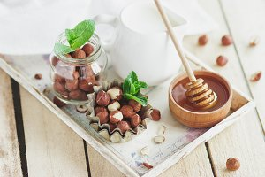 Honey in the wooden bowl, mint leaves, hazelnuts and jar with milk on the wooden tray