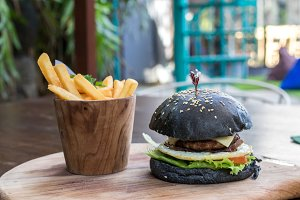 Black burger with meat patty, cheese, tomatoes, mayonnaise, french fries in a wooden plate. Modern fast food lunch.