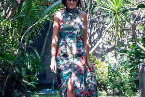 Attractive young woman in a beautiful silk dress among the tropical plants. Vacation. Tropics. Fashion shot. Bali island.