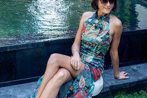 Young sexy woman in a beautful dress near the swimming pool on a luxury villa, Bali island.