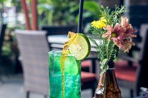 Glass of green refreshing lemonade with lime on top. Bali island.
