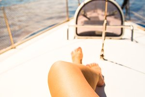 The legs of a woman on the background of a yacht and the sea.