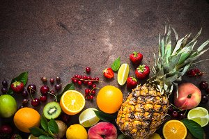 Fruit and berries over dark stone table.
