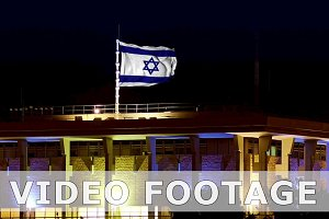 Knesset with flying waving Israel flag at night
