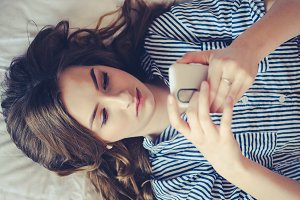 Closeup of pretty teenage girl lying in bed an looking at her mobile phone