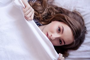 Beautiful young woman lying down in the bed