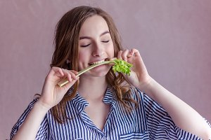 Beautiful girl eating celery