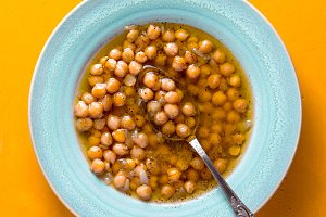 Greek chickpea soup in the white plate on the yellow background  vertical