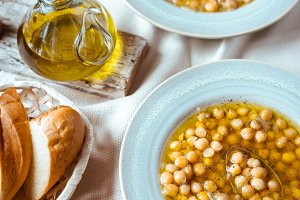 Greek chickpea soup in the white wooden table vertical