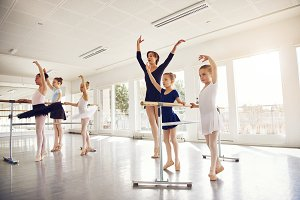 Woman teaching little ballerinas in ballet class