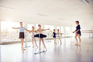 Woman watching practicing group of girls in ballet class
