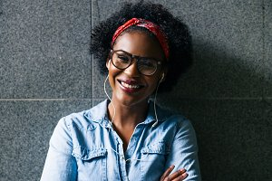 Smiling young African woman standing against a wall
