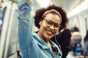 Smiling young African woman riding the train listening to music