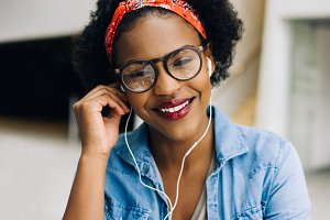 Smiling young African female entrepreneur listening to music at work
