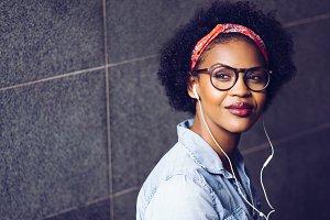 Stylish young woman listening to music on earphones