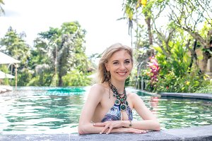 Sexy Beautiful woman sunbathing in swimming pool. Luxury model at the pool.