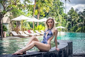 Sexy slim woman at the swimming pool of tropical villa, Bali island, Indonesia.