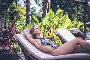 Sexy slim woman at the swimming pool of tropical villa, Bali island, Indonesia.