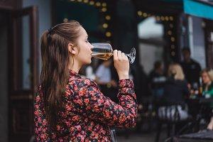 girl drinks wine in a street cafe