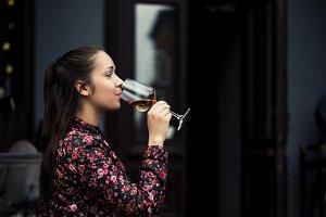 Stylish young girl drinks wine