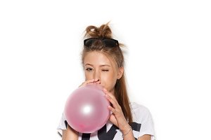 Woman blowing pink balloon