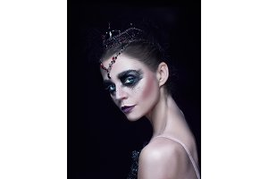 Portrait of the ballerina as swan on black background