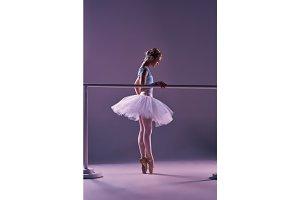 classic ballerina posing at ballet barre