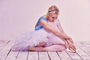 Tired ballet dancer sitting on the wooden floor