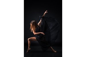 Young beautiful dancer in beige dress dancing on black background