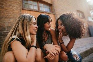 Female friends sitting by street