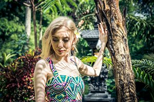 Beautiful slender woman among tropical plants. Beauty, fashion. Spa, healthcare. Tropical vacation. Bali island.