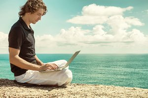 Man working with laptop sitting on the rocky mountain on beautiful clouds seascape background. Freelance concept.