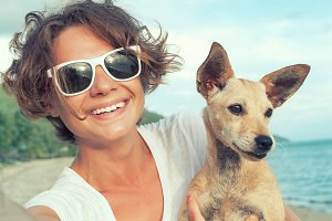 Young attractive girl with her pet dog making selfie on the tropical beach